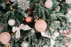 Árbol de navidad adornado con los juguetes en el color de plata y rosado En él vemos los globos con de las cintas y las luces Fotos de archivo