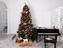 Árbol de navidad adornado con los juguetes, las luces y la partitura fotos de archivo libres de regalías