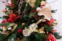 Árbol de navidad adornado con los juguetes, las luces y la partitura imagen de archivo libre de regalías