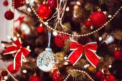 Árbol de navidad adornado con los juguetes y las cintas rojos Fotografía de archivo libre de regalías