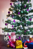 Árbol de navidad adornado con los regalos alrededor y con del cand encendido Fotos de archivo libres de regalías