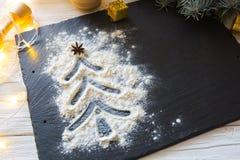 Árbol de navidad adornado con nieve de la harina en el negro en fondo del tablero de la comida de la pizarra Feliz Navidad y Feli Imagenes de archivo