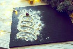Árbol de navidad adornado con nieve de la harina en el negro en fondo del tablero de la comida de la pizarra Feliz Navidad y Feli Imágenes de archivo libres de regalías
