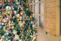 Árbol de navidad adornado e iluminado contra casa de madera Fotografía de archivo