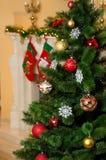 Árbol de navidad adornado en la sala de estar al lado de la chimenea Imagen de archivo libre de regalías