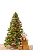 Árbol de navidad adornado en una alfombra con los regalos Fotografía de archivo
