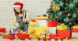 Árbol de navidad adornado mujer asiática por las luces almacen de video