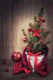Árbol de navidad adornado y chucherías rojas en fondo de madera Foto de archivo libre de regalías