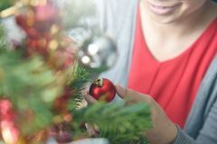 Árbol de navidad de adornamiento femenino asiático con la bola roja Fotos de archivo libres de regalías