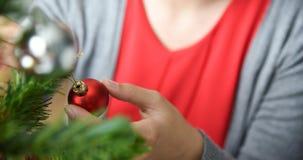 Árbol de navidad de adornamiento femenino asiático con la bola roja Fotos de archivo