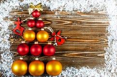 Árbol de navidad, alineado con rojo y bolas del árbol de navidad del oro Foto de archivo libre de regalías