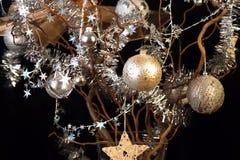 Árbol de navidad, bolas de oro y de plata, cadenas y estrellas en negro Foto de archivo