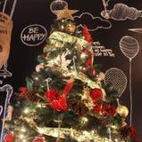 Árbol de navidad brillante por completo de la decoración delante del Wa negro Imagenes de archivo