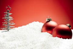 Árbol de navidad cerca de bolas rojas de la decoración en nieve Foto de archivo