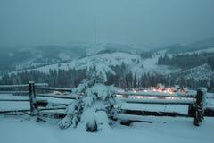 Árbol de navidad cerca de la cerca de madera Luces de la naturaleza y del pueblo del invierno Paisaje Foto de archivo libre de regalías