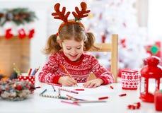Árbol de navidad cercano casero de santa de la letra de la escritura de la muchacha del niño Fotos de archivo