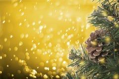 Árbol de navidad con el cono del pino de las decoraciones en bokeh del oro Foto de archivo