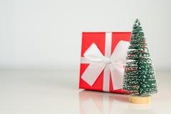 Árbol de navidad con la actual caja roja en el fondo blanco, concepto de los días de fiesta de la tarjeta de felicitación La Navi Fotos de archivo libres de regalías