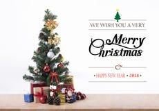 Árbol de navidad con la caja de regalo de las decoraciones y la Feliz Navidad Imagen de archivo libre de regalías