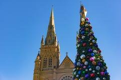 Árbol de navidad con la catedral católica, iglesia en el fondo Imagenes de archivo