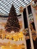 Árbol de navidad con la decoración del oro en alameda de compras imágenes de archivo libres de regalías