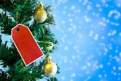Árbol de navidad con la escritura de la etiqueta roja Imágenes de archivo libres de regalías