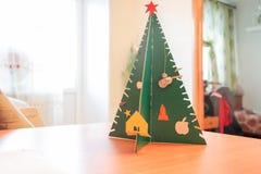 Árbol de navidad con la estrella roja y decoraciones hechas del papel en una tabla Hecho en estilo primitivo por un niño Fotografía de archivo libre de regalías