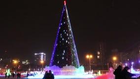 Árbol de navidad con la gente de la iluminación y el caminar que iguala en el invierno, ondulación permanente, Rusia metrajes