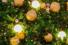 Árbol de navidad con la luz de oro y el fondo chispeante del ornamento Fotografía de archivo
