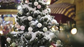 Árbol de navidad con la nieve artificial adornada con los juguetes blancos del árbol de navidad almacen de video