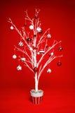 Árbol de navidad con las chucherías rojas y blancas Fotos de archivo