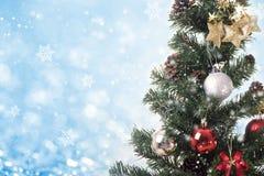 Árbol de navidad con las decoraciones y copo de nieve en bokeh azul Foto de archivo libre de regalías