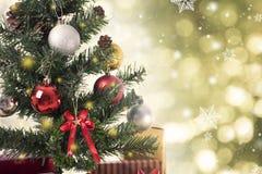 Árbol de navidad con las decoraciones y copo de nieve en bokeh del oro Foto de archivo libre de regalías