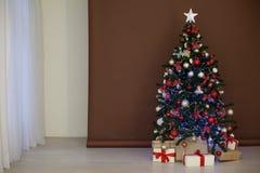 Árbol de navidad con las guirnaldas en los regalos blancos marrones del Año Nuevo del fondo Imagen de archivo