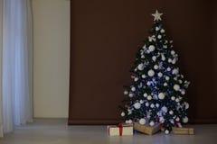 Árbol de navidad con las guirnaldas en los regalos blancos marrones del Año Nuevo del fondo Imágenes de archivo libres de regalías