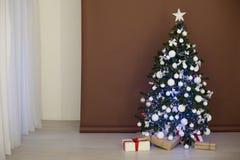 Árbol de navidad con las guirnaldas en los regalos blancos marrones del Año Nuevo del fondo Fotografía de archivo