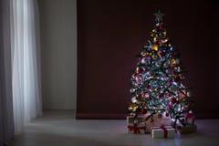 Árbol de navidad con las guirnaldas en los regalos blancos marrones del Año Nuevo del fondo Fotografía de archivo libre de regalías
