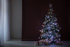 Árbol de navidad con las guirnaldas en los regalos blancos marrones del Año Nuevo del fondo Fotos de archivo