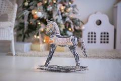 Árbol de navidad con las guirnaldas, los juguetes del vintage y el firepl decorativo Foto de archivo