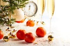 Árbol de navidad con las mandarinas, el champán y el reloj Imagen de archivo