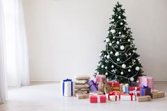 Árbol de navidad con los juguetes del invierno de los días de fiesta del Año Nuevo de los presentes imagen de archivo