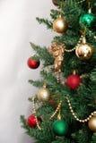 Árbol de navidad con los juguetes y un ángel de oro aislados en los vagos blancos Imagen de archivo