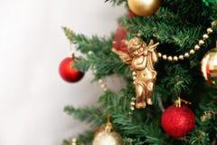 Árbol de navidad con los juguetes y un ángel de oro aislados en los vagos blancos Foto de archivo libre de regalías