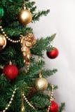 Árbol de navidad con los juguetes y un ángel de oro aislados en los vagos blancos Fotografía de archivo