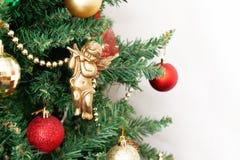 Árbol de navidad con los juguetes y un ángel de oro aislados en los vagos blancos Foto de archivo