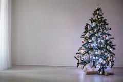 Árbol de navidad con los ornamentos en un Año Nuevo de la Navidad blanca del fondo Imagen de archivo libre de regalías