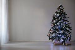Árbol de navidad con los ornamentos en un Año Nuevo de la Navidad blanca del fondo Fotografía de archivo
