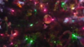 Árbol de navidad con los ornamentos y las luces que centellean con efecto de la falta de definición metrajes