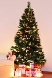 Árbol de navidad con los presentes debajo en sala de estar Fotos de archivo