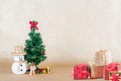 Árbol de navidad con los regalos en fondo del oro Foto de archivo libre de regalías